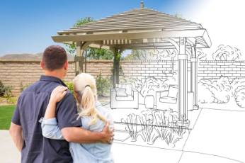 couple watches as their pergola is being built by Newcastle Carports